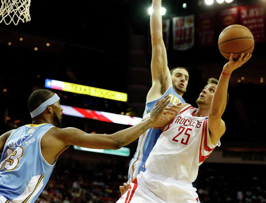 The Houston Rockets Chandler Parson right, is double teamed by the Denver Nuggets Corey Brewer left, and Kosta Koufos center, during the second quarter of NBA game action at the Toyota Center Wednesday, Nov. 7, 2012, in Houston. Photo: James Nielsen, Chronicle / © Houston Chronicle 2012