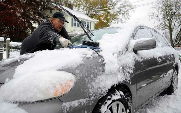 Mark Palmer cleans off a car in Stamford, Conn., on Thursday, November 8, 2012. Photo: Lindsay Niegelberg / Stamford Advocate
