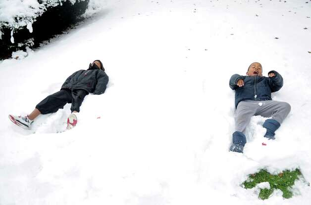Damani Taylor, 9, left, and his brother, Shamar, 6, right, make snow angels in Stamford, Conn., on Thursday, November 8, 2012. Photo: Lindsay Niegelberg / Stamford Advocate