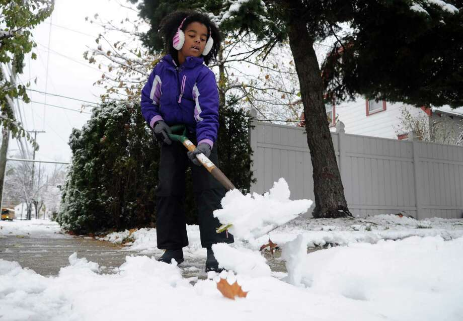 Kayla Williamson, 7, helps shovel her driveway and sidwalk in Stamford, Conn., on Thursday, November 8, 2012. Photo: Lindsay Niegelberg / Stamford Advocate