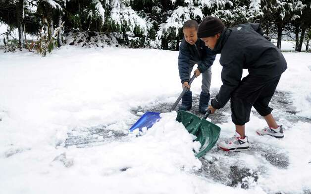 Shamar Taylor, 6, left, and his brother, Damani, 9, right, help shovel their driveway in Stamford, Conn., on Thursday, November 8, 2012. Photo: Lindsay Niegelberg / Stamford Advocate