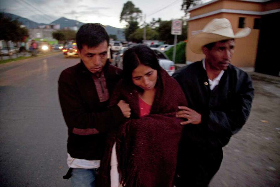 The relatives of Rosa Ramos, who died in the earthquake, walk together as they transport Ramos' body