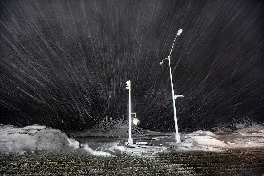 NEW YORK, NY - NOVEMBER 07:  Snow blows past debris and nonfunctioning streetlights during a Nor'Easter snowstorm on November 7, 2012 in the Rockaway neighborhood of the Queens borough of New York City. The Rockaway Peninsula was especially hard hit by Superstorm Sandy and some are evacuating ahead of the coming storm. Photo: Mario Tama, Getty Images / 2012 Getty Images