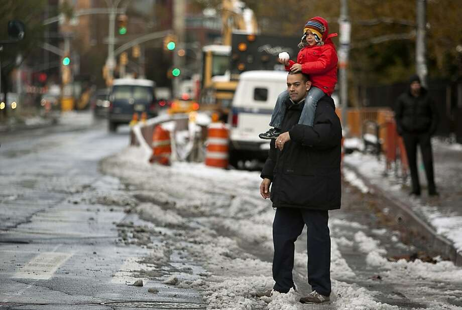 A man and child wait to cross the street after last night's Nor'easter, also known as a northeaster storm, November 8, 2012 in New York City. The storm brought gusting winds, rain, and snow and forced the cancelation of flights for thousands of passengers flying into and out of JFK, LaGuardia and Newark. Photo: Allison Joyce, Getty Images