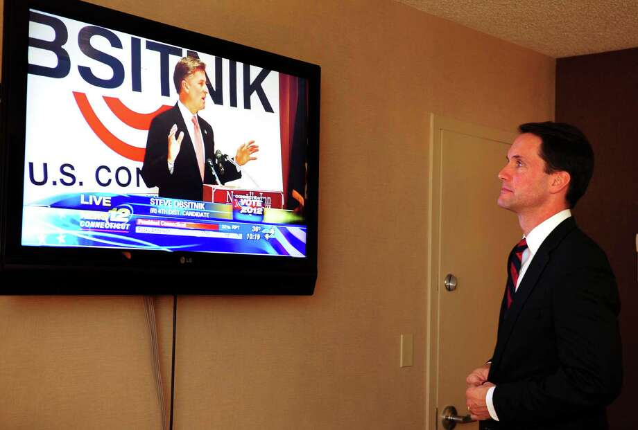 Incumbent Congressman Jim Himes (D-4th) watches in his room at the Bridgeport Holiday Inn as Republican Steve Obsitnik of Westport gives his concession speech. Himes won Obsitnik's hometown handily. Photo: Autumn Driscoll / Connecticut Post