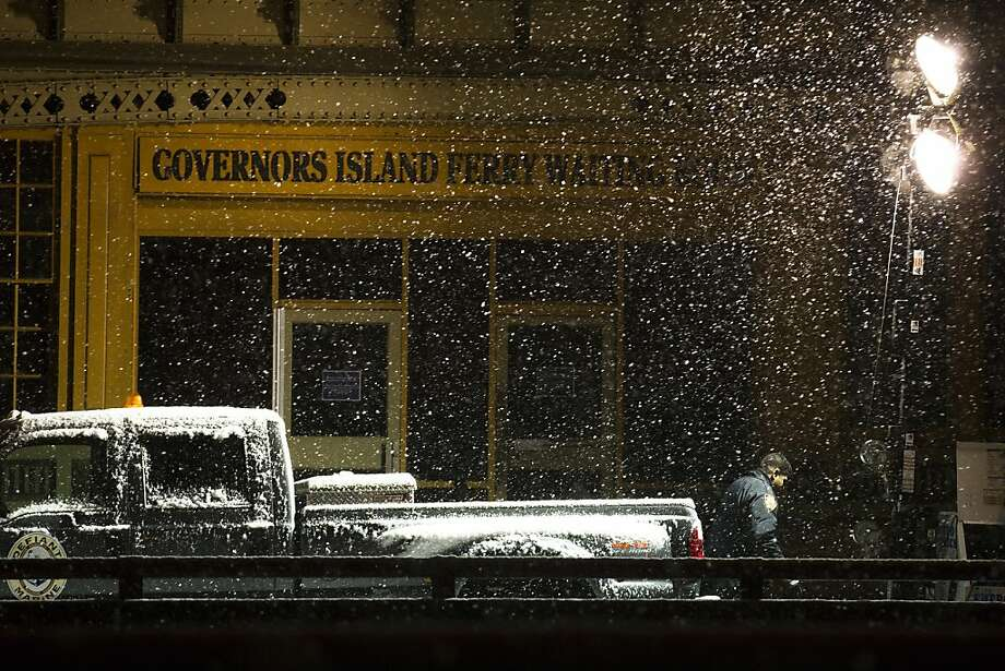 An NYPD police officer stands in the blowing sleet and snow outside the Governors Island Ferry in the Financial District, Wednesday, Nov. 7, 2012, in New York. Residents of New York and New Jersey who were flooded out by Superstorm Sandy are waiting with dread Wednesday for the second time in two weeks as another, weaker storm heads toward them and threatens to inundate their homes again or simply leave them shivering in the dark for even longer. Photo: John Minchillo, Associated Press