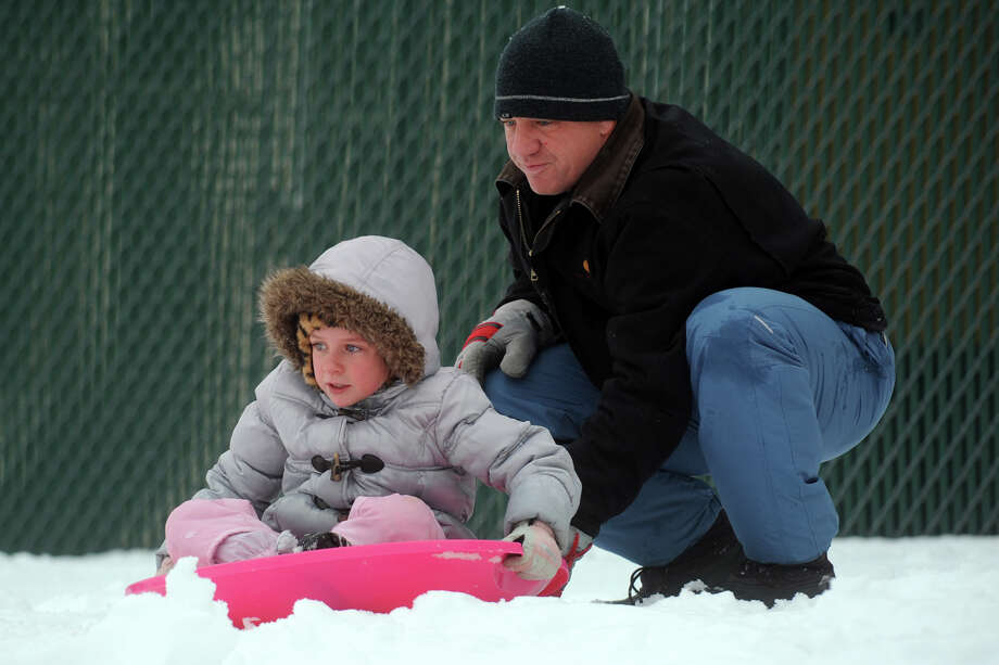 Jocelyn Ciotti, 7, gets ready to sled down a hill next to Flood Middle School, in Stratford, Conn., Nov. 8th, 2012. Jocelyn is seen here with her father, Robert. Photo: Ned Gerard / Connecticut Post