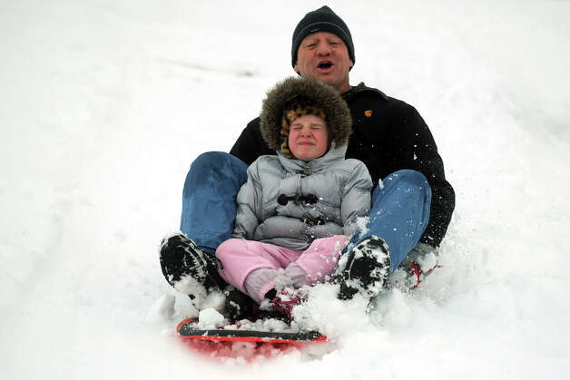 Robert Ciotti and his daughter, Jocelyn, 7, sled down a hill next to Flood Middle School, in Stratford, Conn., Nov. 8th, 2012. Photo: Ned Gerard / Connecticut Post