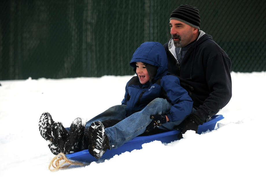 Paul Mushala and his son, Paul Jr., 6, sled down a hill next to Flood Middle School, in Stratford, Conn., Nov. 8th, 2012. Photo: Ned Gerard / Connecticut Post