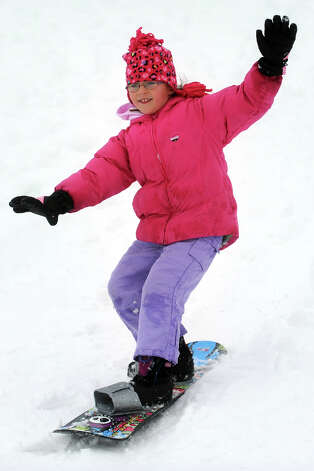 Natalie Farrell, 7, rides a snow board down a hill next to Flood Middle School, in Stratford, Conn., Nov. 8th, 2012. Photo: Ned Gerard / Connecticut Post