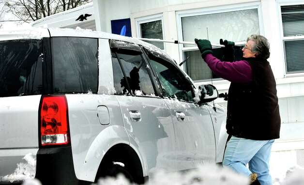 Pat Kearney clears snow from her car in Danbury Thursday, Nov. 8, 2012. Photo: Michael Duffy / The News-Times