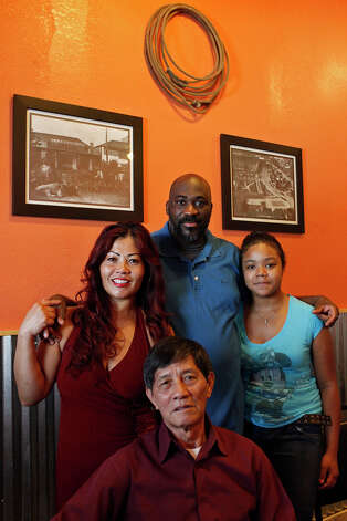 Thomas Howard stands with his wife, Kongsy Howard, their daughter, Katahri Howard, 13, and Kongsy's father, Khampheng Chanthadara, at Long Tieng Lao/American BBQ restaurant in San Antonio on Saturday, Nov. 3, 2012. Photo: Lisa Krantz, San Antonio Express-News / © 2012 San Antonio Express-News