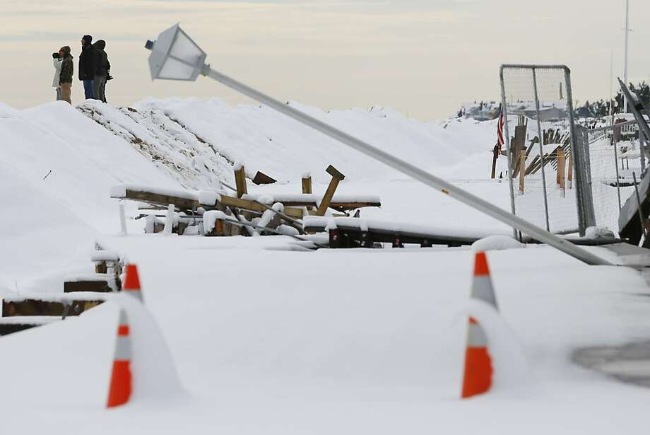 People stand on a dune covered in snow Thursday, Nov. 8, 2012, in Point Pleasant, N.J.,  as a downed street light toppled by   Superstorm Sandy lies in the foreground.    The dune was created for protection from the nor'easter  that rolled through the damaged beachfront town Wednesday. Photo: Julio Cortez, Associated Press