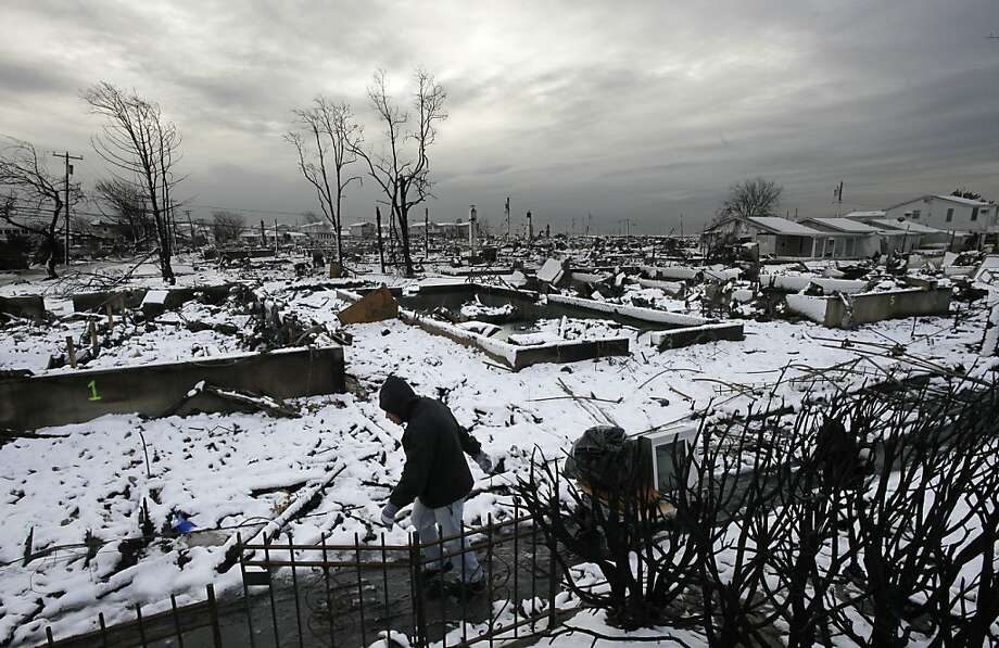 Damon Rasinya carts debris from his family home past the fire-scorched landscape of Breezy Point after a Nor'easter snow, Thursday, Nov. 8, 2012 in New York.  The beachfront neighborhood was devastated during Superstorm Sandy when a fire pushed by the raging winds destroyed many homes. Photo: Mark Lennihan, Associated Press