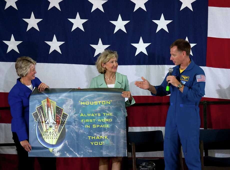 Atlantis shuttle crew member commander Chris Ferguson hands Sen. Kay Bailey Hutchison and Houston Mayor Annise Parker a banner that was flown on space shuttle Atlantis during a homecoming event where hundreds turned out to greet the astronauts at Ellington Field Friday, July 22, 2011. Photo: Johnny Hanson, Houston Chronicle / © 2011 Houston Chronicle