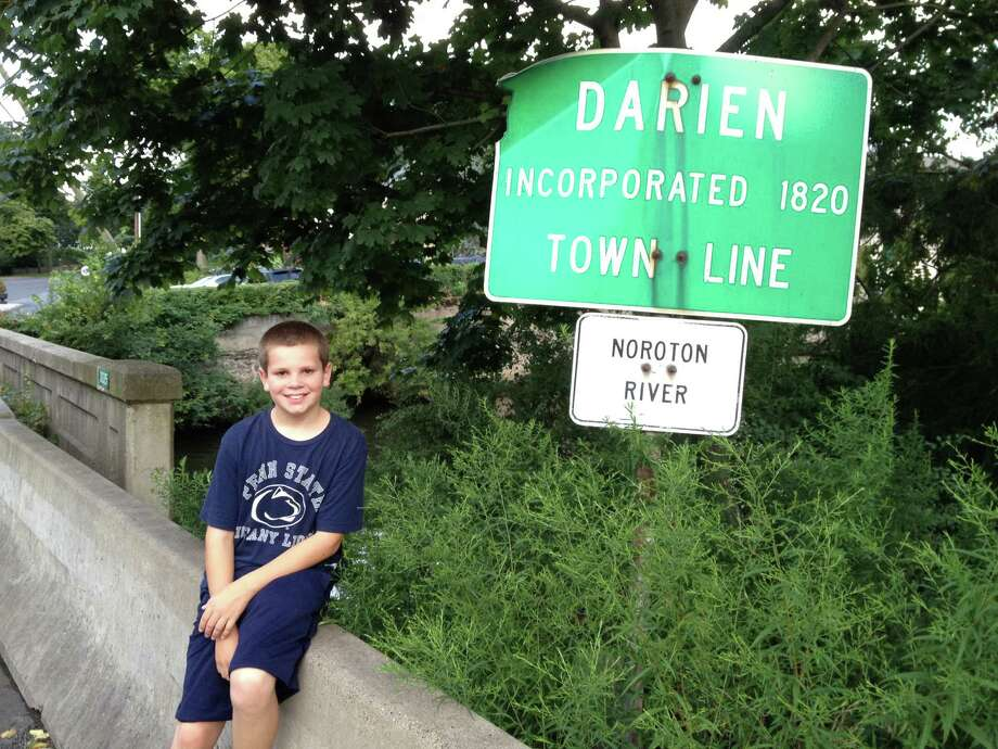 Eleven-year-old Christopher Wilton  sits at the Darien Town line during his walk across Connecticut with his father Chuck. Photo: Contributed