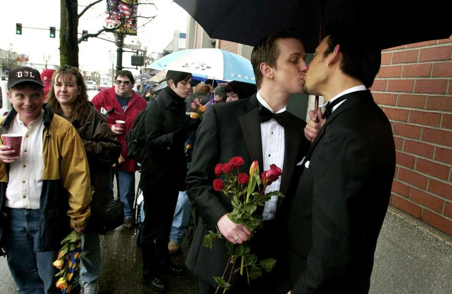 Allows domestic partnerships: OregonSteven Hansen, left, kisses his fiancee, Rick Raymen, as they stand in a line near the Multnomah Building to receive a marriage license Wednesday, March 3, 2004, in Portland, Ore. County officials had issued dozens of licenses to gay couples after deciding that Oregon law allowed the unions. The Oregon Supreme Court voided all same-sex marriage licenses in April 2005.  Photo: MICAHEL LLOYD, AP / THE OREGONIAN