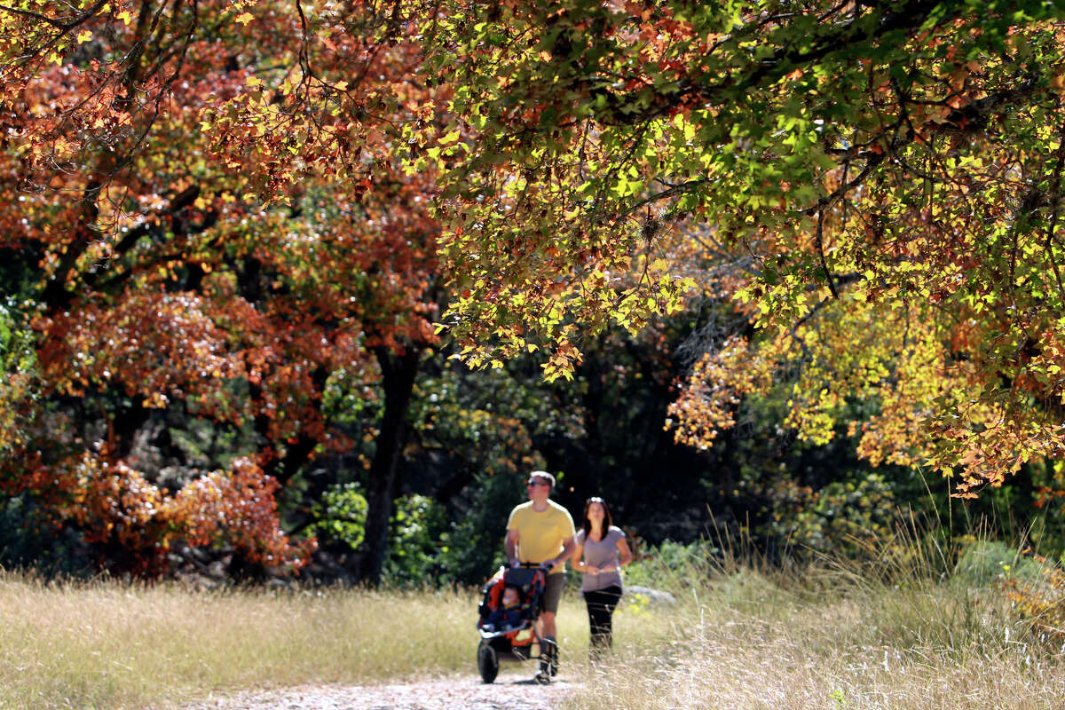 Mike and Rhonda Cosgrove walk in a meadow with their son Colin at Lost Maples State Natural Area.