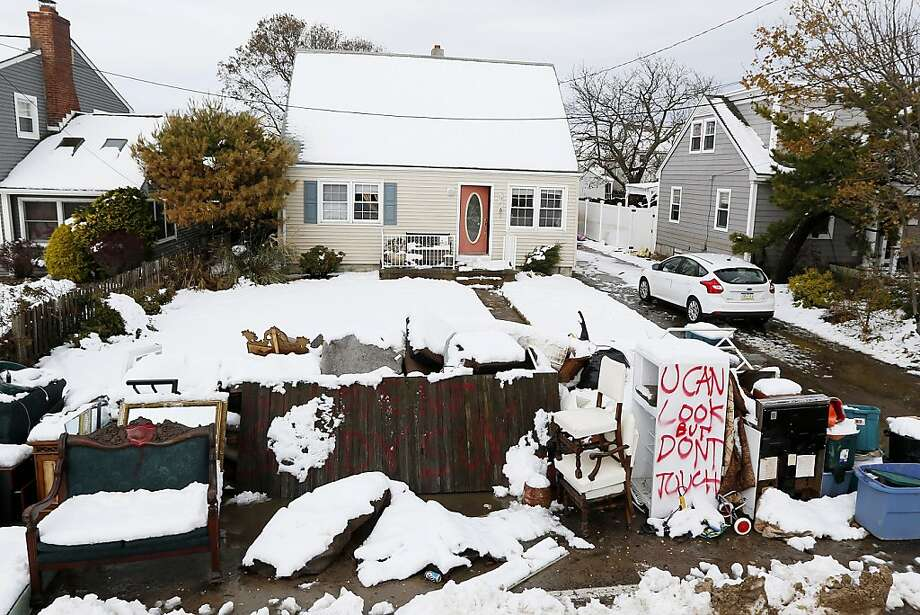 Messages are written on snow covered debris from Superstorm Sandy outside of the Miller residence following a nor'easter storm, Thursday, Nov. 8, 2012, in Point Pleasant, N.J.  The New York-New Jersey region woke up to wet snow and more power outages Thursday after the nor'easter pushed back efforts to recover from Superstorm Sandy, that left millions powerless and dozens dead last week. (AP Photo/Julio Cortez) Photo: Julio Cortez, Associated Press