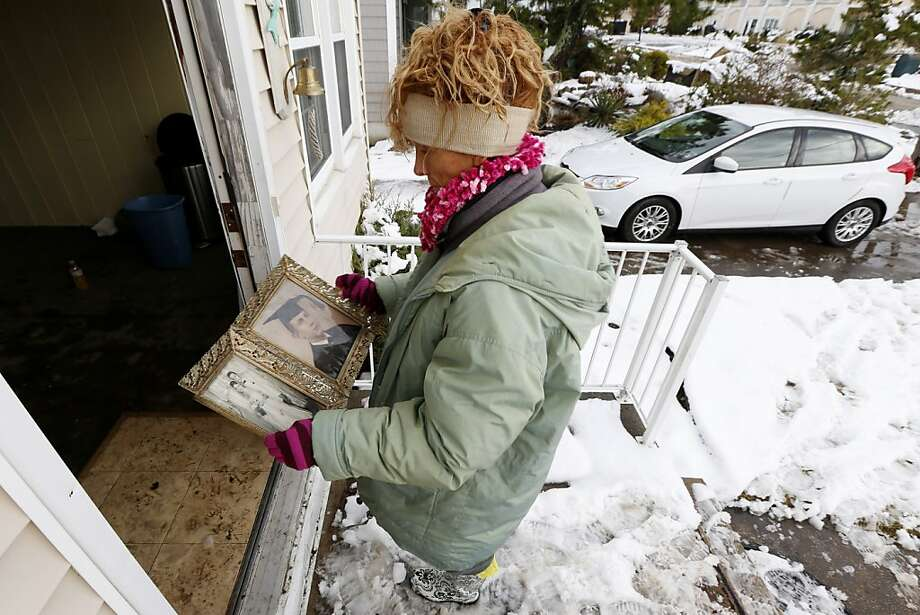 Jeanene Miller holds photographs of her in-laws while trying to dry them out after they were damaged during a flood caused by Superstorm Sandy, Thursday, Nov. 8, 2012, in Point Pleasant, N.J.  The New York-New Jersey region woke up to wet snow and more power outages Thursday after the nor'easter pushed back efforts to recover from Superstorm Sandy, that left millions powerless and dozens dead last week. (AP Photo/Julio Cortez) Photo: Julio Cortez, Associated Press