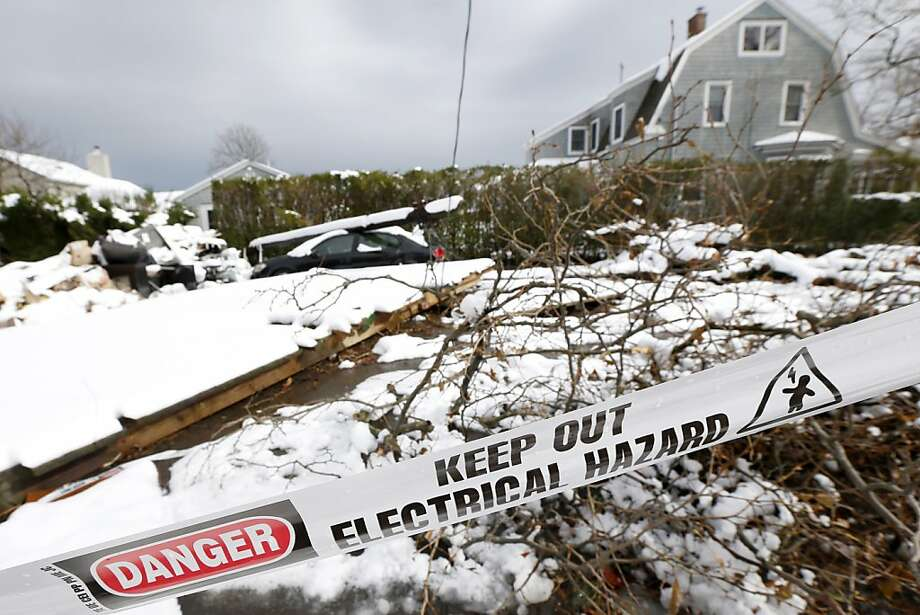 A down utility poll rests on top of a vehicle as snow covered debris from Superstorm Sandy lay in the middle of a street following a nor'easter storm, Thursday, Nov. 8, 2012, in Point Pleasant, N.J.  The New York-New Jersey region woke up to wet snow and more power outages Thursday after the nor'easter pushed back efforts to recover from Superstorm Sandy, that left millions powerless and dozens dead last week. (AP Photo/Julio Cortez) Photo: Julio Cortez, Associated Press