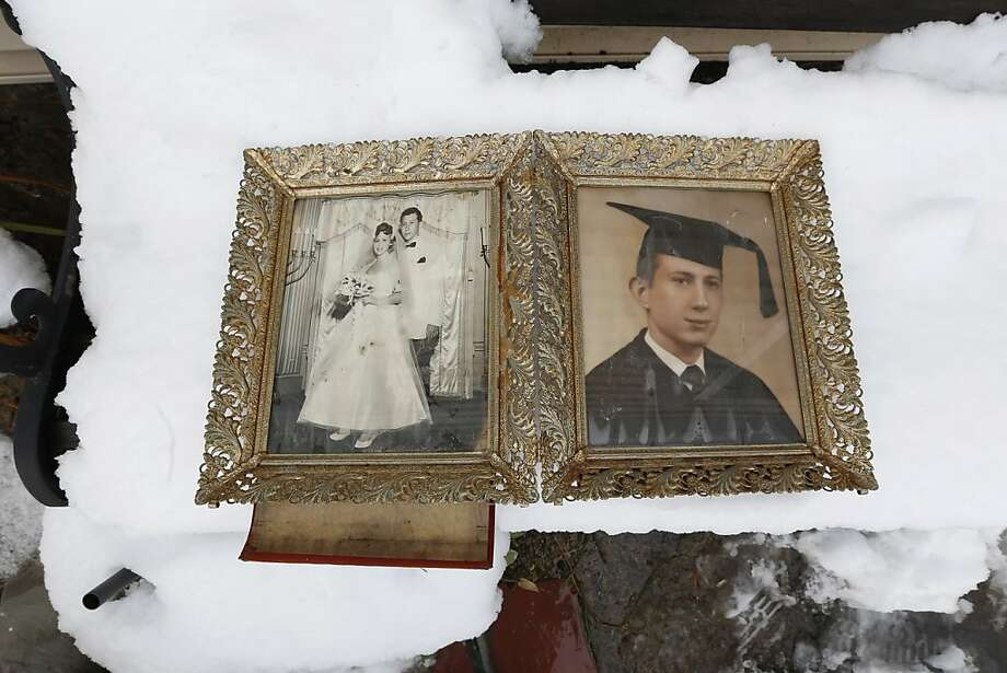 Photographs of Elliott Miller's wedding day and graduation lay on a snow covered bench as Jeanene Miller tries to dry out the pictures of her in-laws which were damaged during floods caused by Superstorm Sandy, Thursday, Nov. 8, 2012, in Point Pleasant, N.J.  The New York-New Jersey region woke up to wet snow and more power outages Thursday after the nor'easter pushed back efforts to recover from Superstorm Sandy, that left millions powerless and dozens dead last week. (AP Photo/Julio Cortez) Photo: Julio Cortez, Associated Press