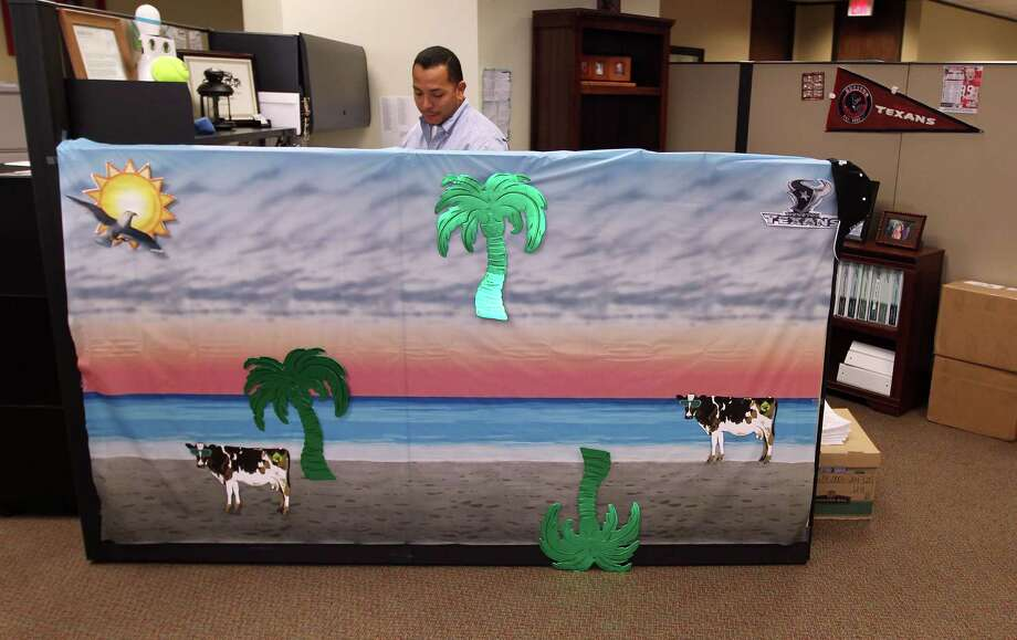 It's almost a day at the beach for Chesmar Homes warranty administrator Christian Del Rio, with his tropical-themed cubicle. Photo: James Nielsen, Staff / © Houston Chronicle 2012
