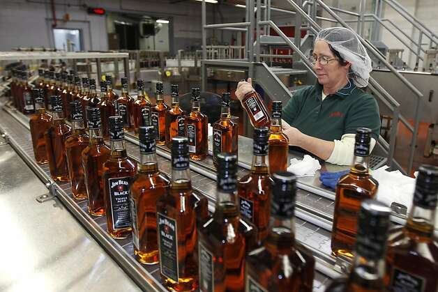 Mary Carney, a Jim Beam Brands Co. employee, checks the label quality on bottles of Jim Beam Black bourbon whiskey at their distillery in Clermont, Kentucky, U.S., on Tuesday, Feb. 8, 2011. Photo: John Sommers II, Bloomberg