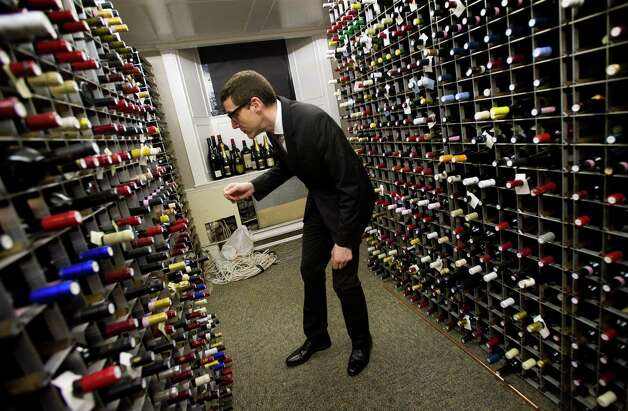 Patrick Cappiello, the wine director, or sommelier, at Gilt, retrieves a 2007 Coche-Dury, Bourgogne Rouge at the restaurant in New York, Nov. 1st, 2012. The sommelier can be a positive force, an interpreter and guide who can shepherd a meal along a rewarding path. Photo: JOSHUA BRIGHT, New York Times / NYTNS