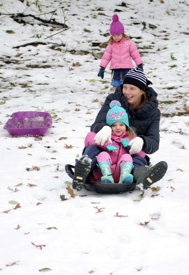 Molly Robotti and her daughter Pearl, 4, sled down a hill as Pearl's sister, Beatrice, 2, watches on Woodridge Drive in Stamford, Conn., on Thursday, November 8, 2012. Photo: Lindsay Niegelberg / Stamford Advocate