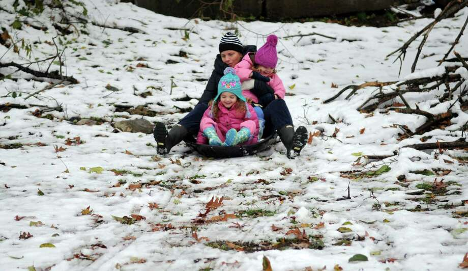 Molly Robotti and her daughters, Beatrice, 2, and Pearl, 4, sled down a hill on Woodridge Drive in Stamford, Conn., on Thursday, November 8, 2012. Photo: Lindsay Niegelberg / Stamford Advocate