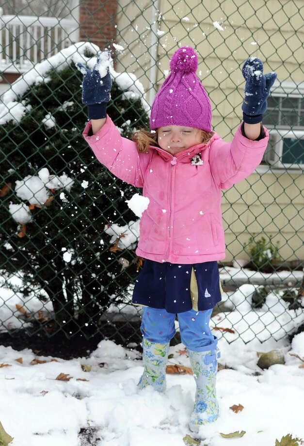 Beatrice Robotti, 2, throws a handfull of snow in the air on Woodridge Drive in Stamford, Conn., on Thursday, November 8, 2012. Photo: Lindsay Niegelberg / Stamford Advocate