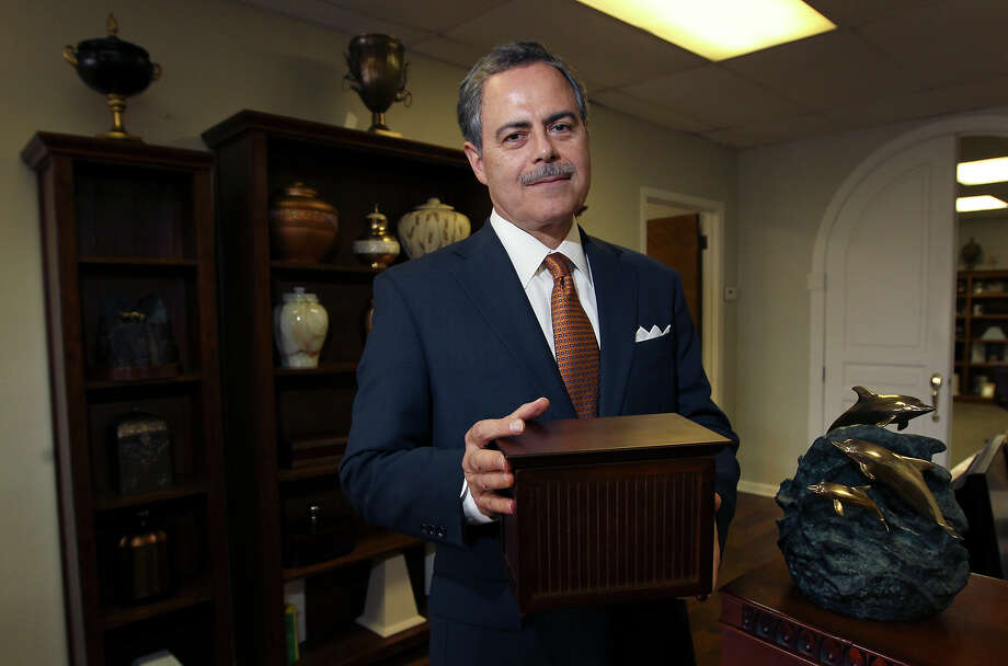Fernando O'Horan, president of Funeral Caring USA, shows a sample of cremation containers that range from a minimal wooden container which cost about $48 to a premium urn which has dolphins artwork which cost about $499. The company along with a consumer group offers a simple cremation for $545. Funeral Caring USA has been in business for 13 years according to O'Horan. Photo: Kin Man Hui, San Antonio Express-News / ©2012 San Antonio Express-News