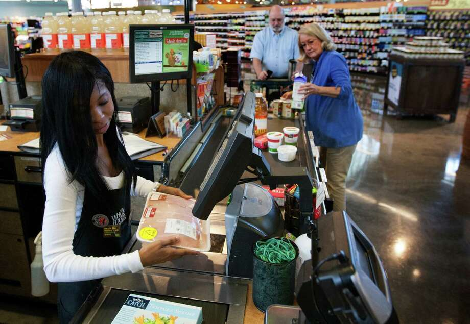 Whole Foods employee Knicole Rink checks out Jean and Jim Eldridge in Sugar Land. Whole Foods started with one store in Austin in 1980 and now has 335 worldwide. Six of those locations are in the Houston area. Photo: J. Patric Schneider, Freelance / © 2012 Houston Chronicle