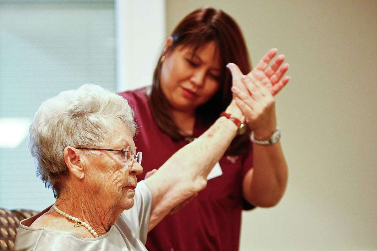 Pam Pallera, a physical therapist with Encompass Home Health, does a shoulder exercise with Fay Allison, a client of Regal Estates of League City.