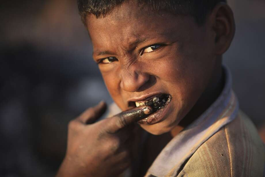 No brush, no toothpaste: A homeless boy cleans his teeth with coal in Jammu, India. Photo: Channi Anand, Associated Press