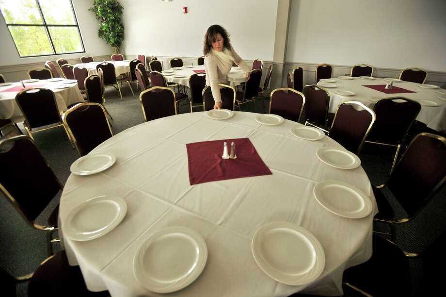 Ruth Ribeiro sets plates out in the conference room on Thursday, Oct. 8, 2012, in preparation for a meeting at the partially remodeled Portuguese Cultural Center in Danbury. The center closed due to heavy snow damage in 2011. Photo: Jason Rearick / The News-Times