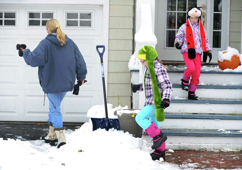 Liz Schumacher leads her daughters, Bailey and Abby, to the car as they head to school from their home on Mill Plain Rd. in Fairfield, Conn. on Thursday, Nov. 8, 2012. Photo: Cathy Zuraw / Connecticut Post