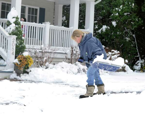 Liz Schumacher shovels the walk at her home on Mill Plain Rd. in Fairfield, Conn. on Thursday, Nov. 8, 2012. Photo: Cathy Zuraw / Connecticut Post