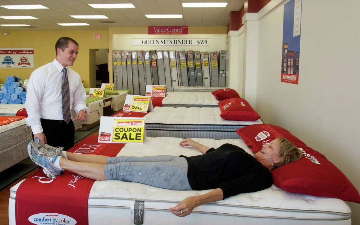Mattress Firm manager Christopher Wilson helps customer Windi Pastorini. The company wants executives and field employees to feel connected.