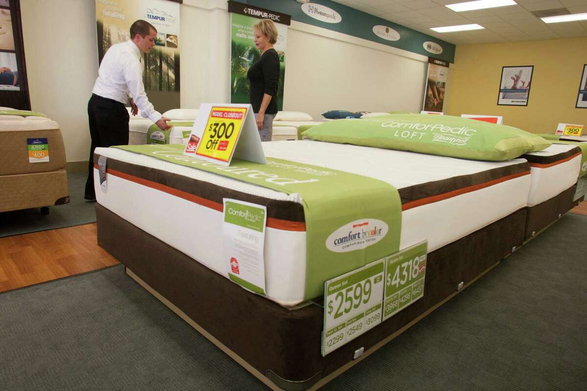 Mattress Firm area manager Christopher Wilson helps customer Windi Pastorini pick out a new mattress on Monday, Sept. 24, 2012, in Houston. ( J. Patric Schneider / For the Chronicle )