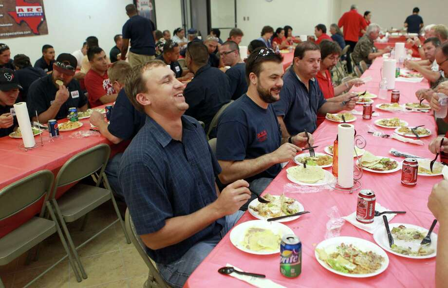 Trey Hoover, left, shares a laugh with his co-workers during a weekly free lunch at ARC Specialties. Photo: Johnny Hanson, Staff / © 2012  Houston Chronicle