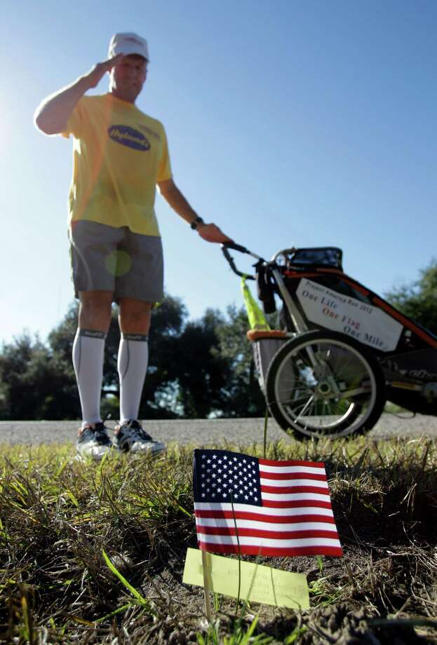 Army veteran Mike Ehredt of Idaho salutes after placing a flag honoring fallen Marine Cpl R. Ashley Joshua, 23, of Rancho Cucamonga, CA during his run along US 90 east of Liberty as part of Project America Run Part II  Thursday, Nov. 8, 2012.  Each mile he stops and plants a US flag that bears the name, age, rank and hometown of a service members killed during the war in Afghanistan. Photo: Melissa Phillip, Houston Chronicle / © 2012 Houston Chronicle