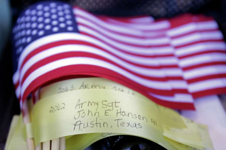 Flag are stacked for Army veteran Mike Ehredt of Idaho to plant along US 90 during his Project America Run Part II  shown Thursday, Nov. 8, 2012 in Liberty. Each mile he stops and plants a US flag that bears the name, age, rank and hometown of a service members killed during the war in Afghanistan. He uses a GPS to keep track of where he puts the flags (which are planted in chronological order of the service members death) and can be tracked at this web address: http://projectamericarun.com/afghlocatemike.htm Photo: Melissa Phillip, Houston Chronicle / © 2012 Houston Chronicle