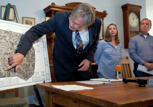 Attorney Brad Rockwell, left, points to a map showing planned development in the Century Oaks subdivision, as Annalisa Peace, center, of the Greater Edwards Aquifer Alliance, and Tom Tobin, president of the Hidden Oaks Homeowners Association, look on, Thursday, Nov. 8, 2012, in San Antonio. Photo: Darren Abate, Darren Abate/For The Express-New