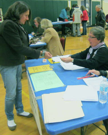 Patricia Lathrope checks in longtime New Milford voter Patrica Luddy to vote on election day, Nov. 6, 2012 at Sarah Noble Intermediate School. Mrs. Luddy was likely casting her final ballot in New Milford since she would soon be moving to California. Photo: Norm Cummings