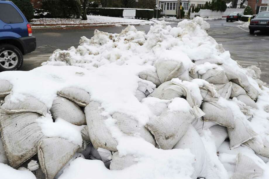 Snow-covered sandbags in the parking lot of the Sound Beach Fire House in Old Greenwich, Thursday afternoon, November 8, 2012, are a reminder of a week of wild weather during which Greenwich was hit with the one-two punch of a hurricane and nor'easter. Photo: Bob Luckey / Greenwich Time