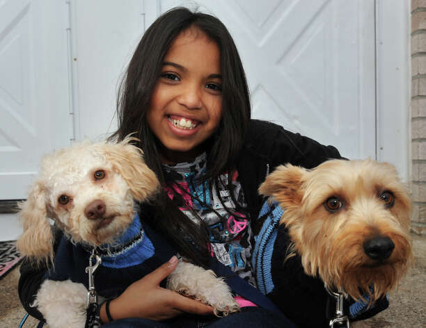 Arianna Rodriguez holds her dogs Skippy and Deuce on the front porch of her Bridgeport, Conn. home Nov. 8th, 2012. Rodriguez has organized a pet food drive in the wake of storm Sandy. Photo: Ned Gerard / Connecticut Post
