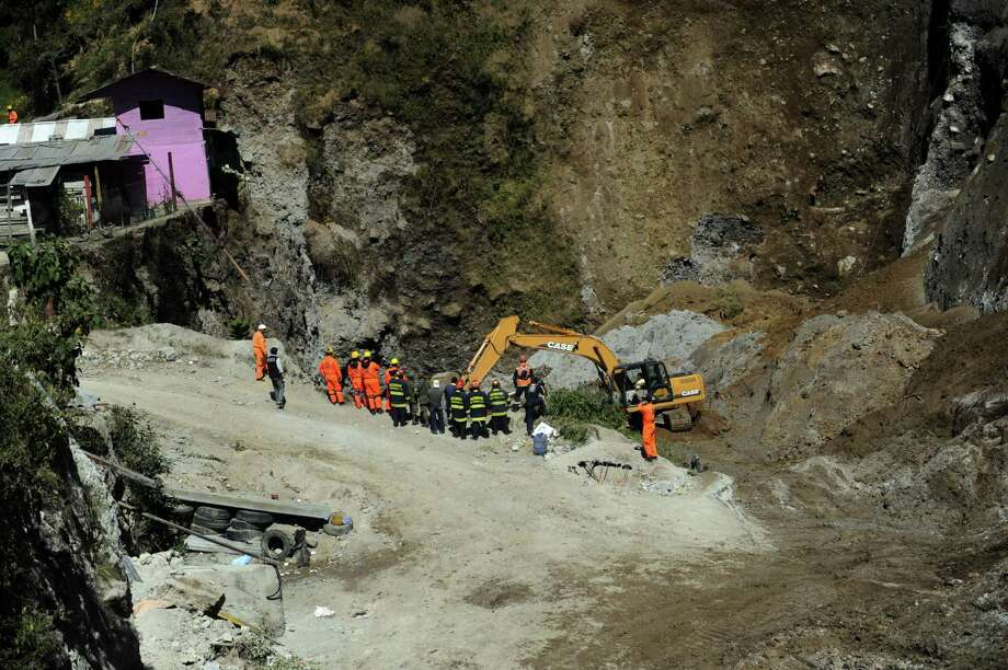 Firefighters with heavy equipment excavate searching people feared buried at a sand mine by an earthquake in San Marcos, 260 km from Guatemala City, on November 8, 2012. AFP PHOTO/Johan ORDONEZ Photo: JOHAN ORDONEZ, AFP/Getty Images / AFP
