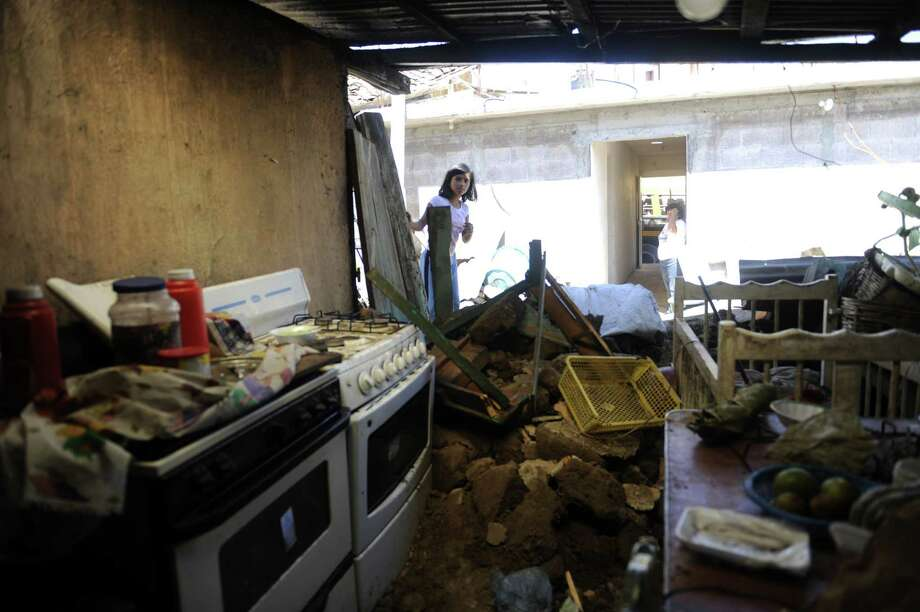 A girls looks inside a house damaged by an earthquake in San Marcos, 260 km from Guatemala City, on November 8, 2012.   AFP PHOTO/Johan ORDONEZ Photo: JOHAN ORDONEZ, AFP/Getty Images / AFP ImageForum